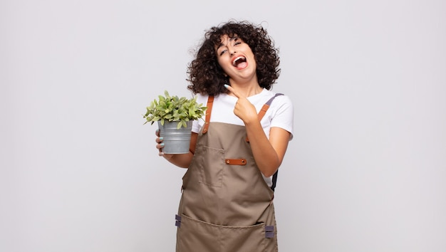 Jeune femme jardinière à l'air excitée et surprise pointant vers le côté et vers le haut pour copier l'espace