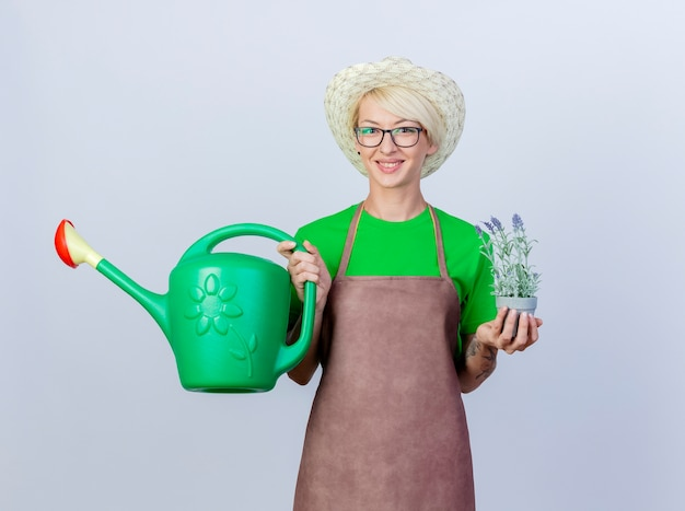 Jeune femme jardinière aux cheveux courts en tablier et chapeau tenant un arrosoir et une plante en pot souriante avec un visage heureux