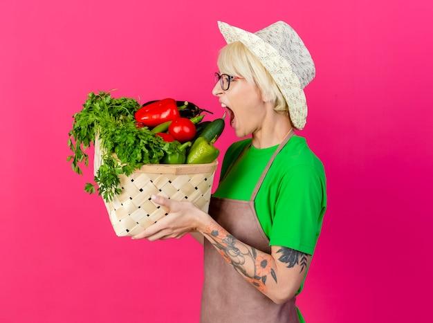 Jeune femme jardinière aux cheveux courts en tablier et chapeau tenant une caisse pleine de légumes