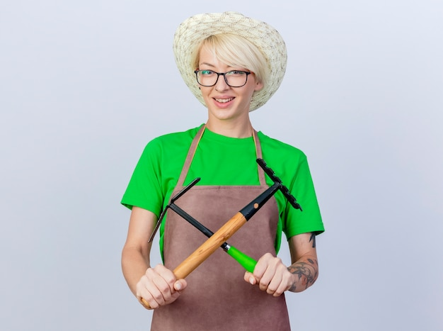 Jeune femme jardinière aux cheveux courts en tablier et chapeau tenant une pioche et un mini râteau croisant les mains souriant joyeusement