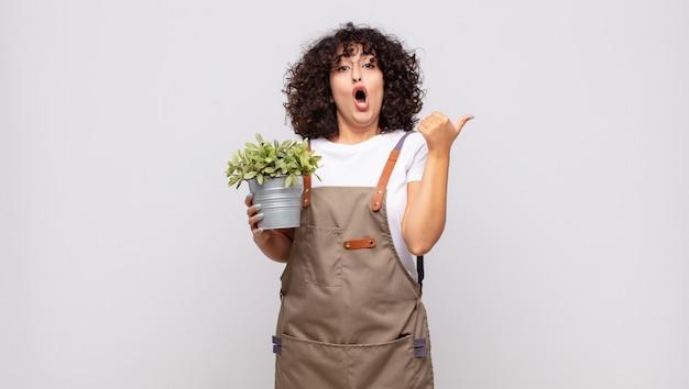 Jeune femme à la jardinière étonné d'incrédulité, pointant sur l'objet sur le côté et disant wow, incroyable