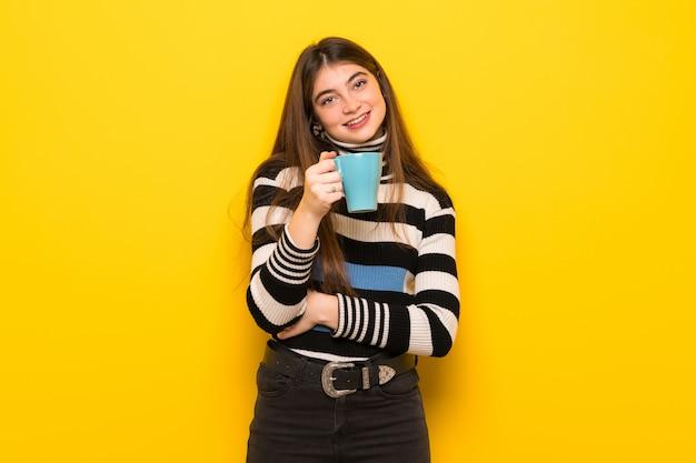 Jeune femme, sur, jaune, mur, tenue, a, chaud, tasse café