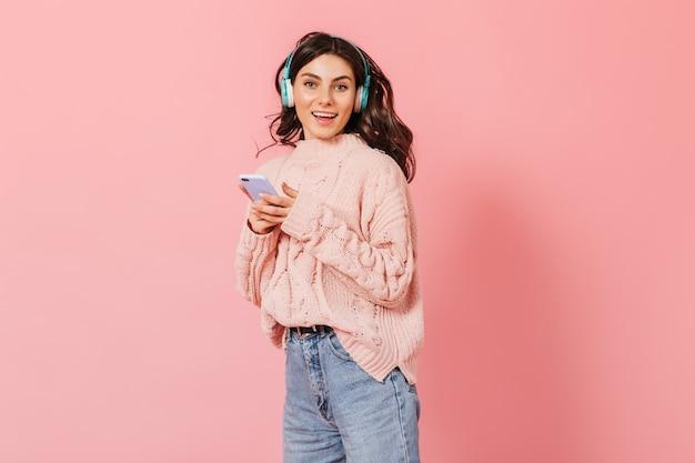 Jeune femme en jeans de couleur claire danse et écoute une chanson joyeuse dans un casque bleu.
