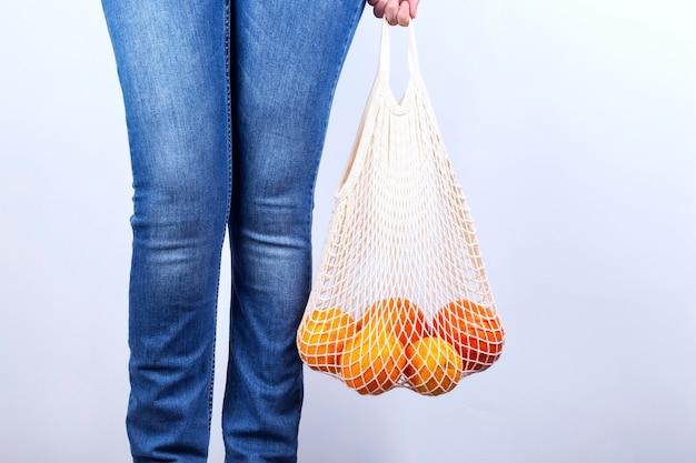 Jeune femme en jeans est sur détient sac à cordes avec divers agrumes sur fond gris. concept zéro déchet, respectueux de l'environnement.