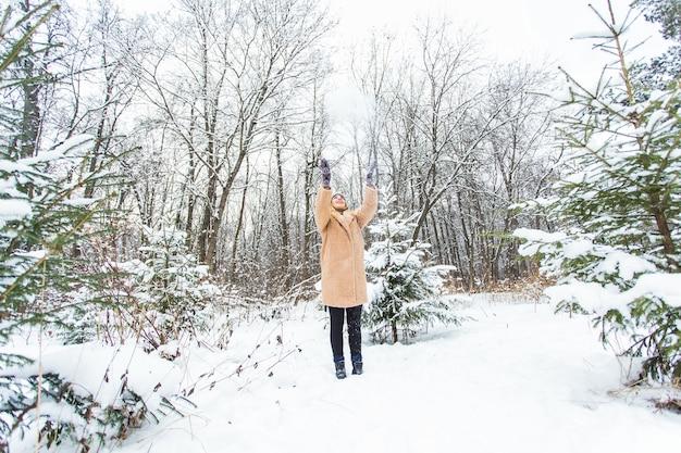 Jeune femme jetant de la neige en l'air lors d'une journée d'hiver ensoleillée, elle est heureuse et amusante.