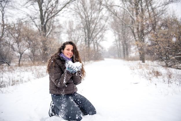 Jeune femme jetant de la neige, heureux et amusant