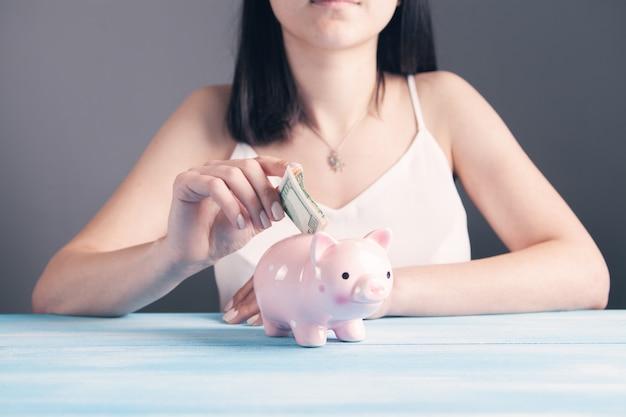Une jeune femme jette un dollar dans une tirelire alors qu'elle est assise devant la table