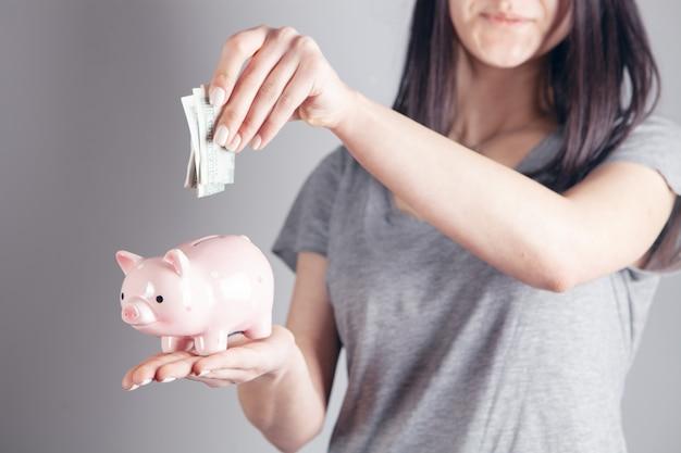 La jeune femme jette le dollar dans la tirelire