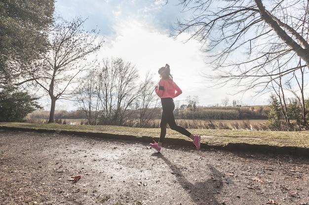 Jeune femme jogging sur le chemin hors route dans la matinée.