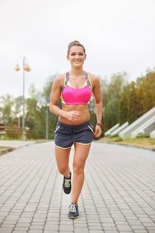 Jeune femme jogging ou courir en plein air