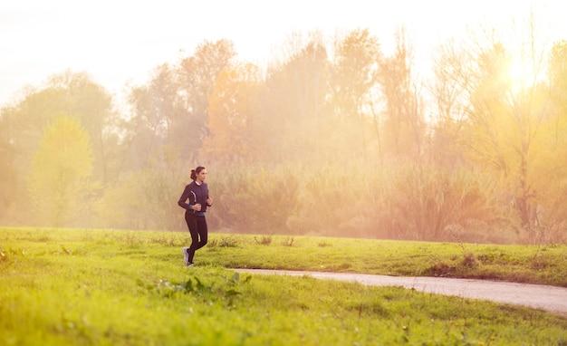 Jeune femme jogging dans le parc au coucher du soleil