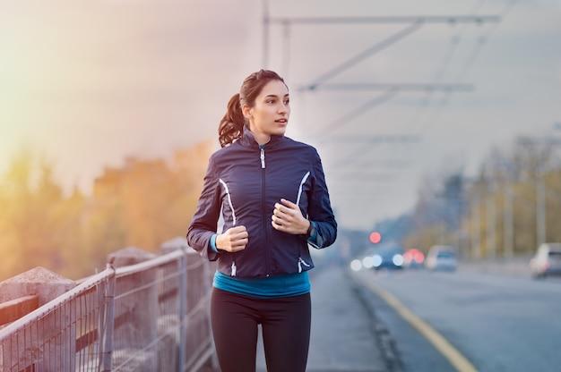 Jeune femme jogging dans la rue tôt le matin