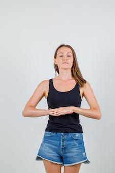 Jeune femme joignant deux mains en maillot noir, short et à la détente. vue de face.