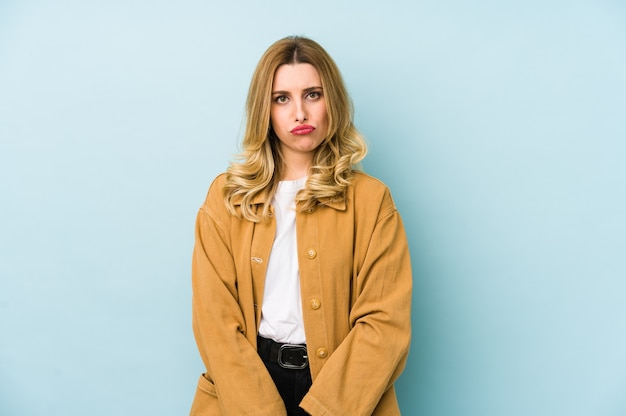 Jeune femme jolie blonde isolée souffle sur les joues, a une expression fatiguée. concept d'expression faciale.