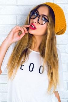 Jeune femme jolie blonde avec des lèvres sexy brillantes, portant des lunettes et un chapeau