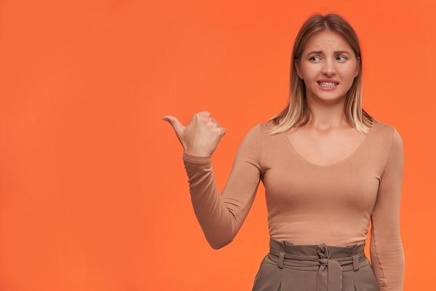 Jeune femme jolie blonde mécontente avec de courts cheveux lâches en gardant sa main levée tout en montrant de côté et en grimaçant son visage, isolé sur un mur orange