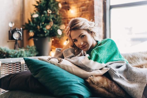 Jeune femme jolie blonde souriante se trouve dans une pièce lumineuse