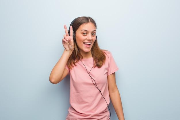 Jeune femme jolie caucasienne amusante et heureuse de faire un geste de victoire. elle écoute de la musique avec des écouteurs.