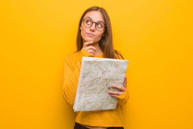 Jeune femme jolie caucasienne doutant et confus. elle tient une carte.