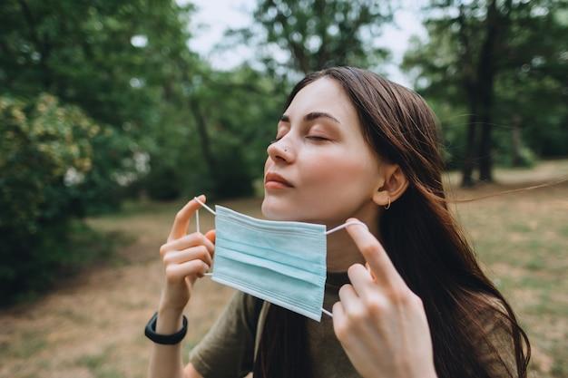 Jeune femme jolie caucasienne enlève un masque de protection médicale de son visage sur la nature, respirant de l'air frais et pur.