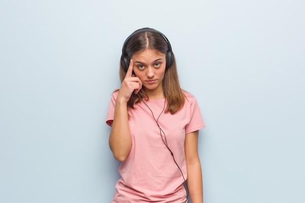 Jeune femme jolie caucasienne pense à une idée. elle écoute de la musique avec des écouteurs.