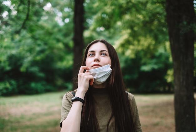 Jeune Femme Jolie Caucasienne Supprime Un Masque De Protection Médicale Sur La Nature, Respirant De L'air Frais Et Pur. Photo Premium