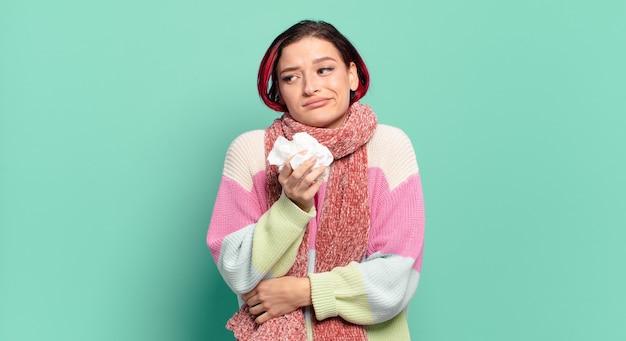 Jeune femme jolie cheveux roux haussant les épaules, se sentant confus et incertain, doutant des bras croisés et regard perplexe concept grippe