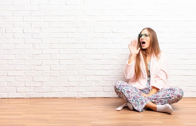 Jeune femme jolie criant fort et avec colère pour copier de l'espace sur le côté, avec la main à côté de la bouche. concept de maison