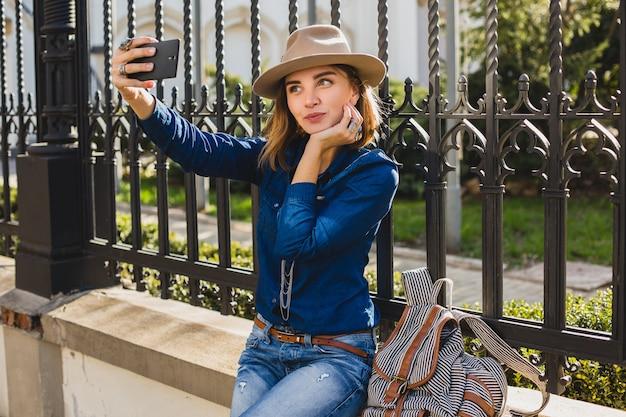 Jeune femme jolie élégante prenant un selfie, vêtue d'une chemise en jean et d'un jean