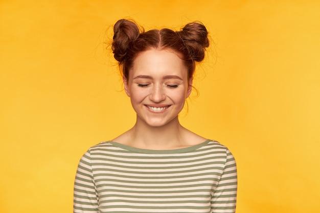 Jeune femme, jolie femme au gingembre avec deux petits pains. porter un pull rayé et avoir l'air excité. se sentir très heureux en ce moment. tenez-vous isolé sur un mur jaune avec les yeux fermés