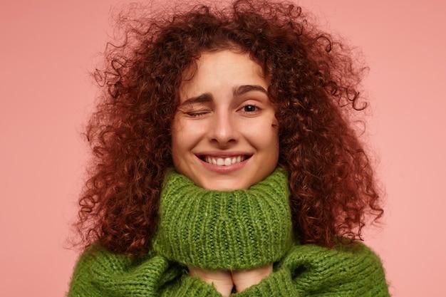 Jeune femme, jolie femme aux cheveux bouclés roux. porter un pull à col roulé vert et mettre les mains en dessous. et clin d'oeil, isolé, gros plan sur un mur rose pastel