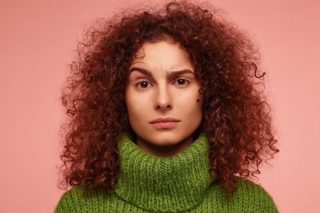 Jeune femme, jolie femme aux cheveux bouclés roux. regard sérieux. vêtu d'un pull à col roulé vert et avec un sourcil levé, isolé, gros plan sur un mur rose pastel