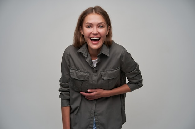 Jeune femme, jolie femme aux cheveux longs bruns. portant une chemise grise et riant fort, touchant son ventre. écoutez une blague de grille. regarder la caméra isolée sur fond gris