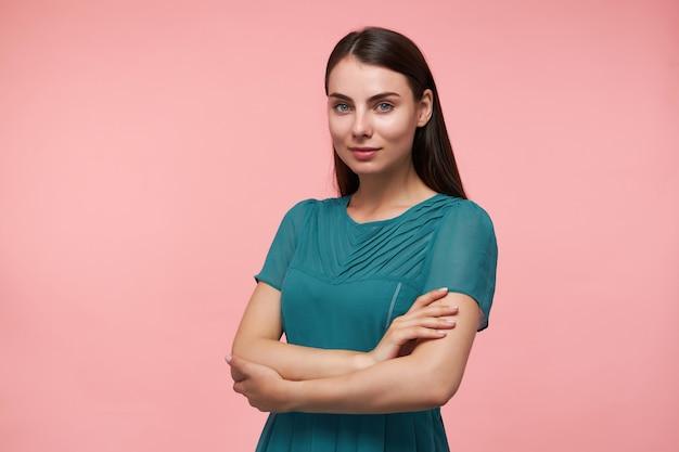 Jeune femme, jolie femme aux longs cheveux bruns. plier les mains sur un coffre. porter une robe émeraude. regarder et sourire isolé sur mur rose pastel