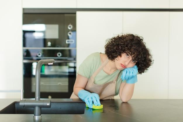 Jeune femme jolie femme de ménage laver la vaisselle à la maison