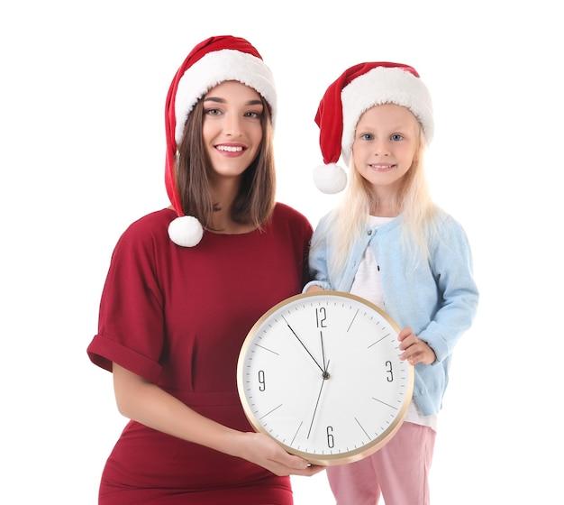 Jeune femme et jolie fille en bonnets de noel avec horloge sur fond blanc. notion de compte à rebours de noël