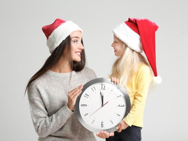 Jeune femme et jolie fille en bonnets de noel avec horloge sur une surface claire