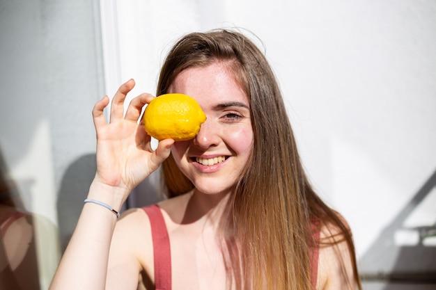 Jeune femme jolie et heureuse en robe d'été décontractée assise sur une terrasse et couvrant les yeux avec du citron mûr