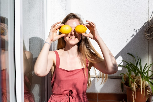 Jeune femme jolie et heureuse en tenue d'été décontractée assise sur une terrasse et se couvrant les yeux avec des citrons mûrs