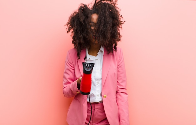 Jeune femme jolie noire avec un coiffeur contre le mur rose