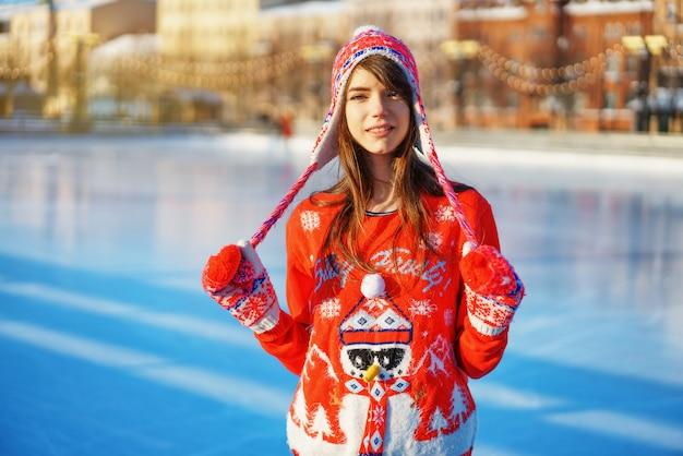 Jeune femme jolie patinage sur glace en hiver