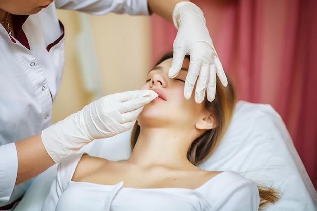 Jeune femme jolie recevant des traitements dans des salons de beauté.