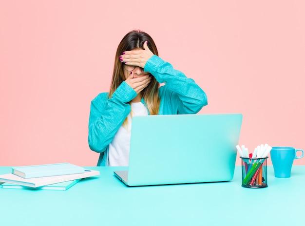 Jeune femme jolie travaillant avec un ordinateur portable couvrant le visage avec les deux mains disant non à la caméra! refuser des photos ou interdire des photos