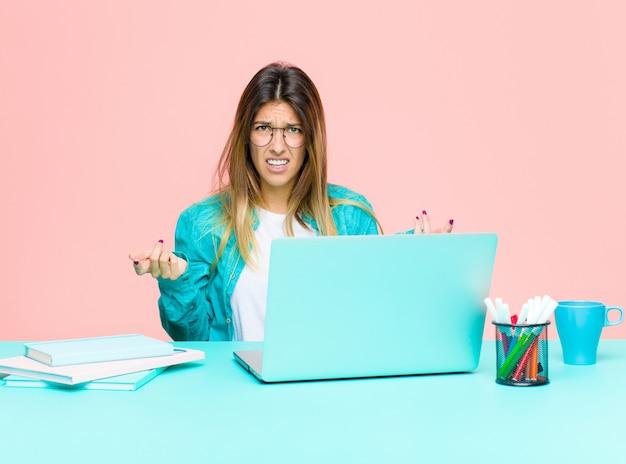 Jeune femme jolie travaillant avec un ordinateur portable se sentant désemparée et confuse, ne sachant pas quel choix ou option choisir, se demandant