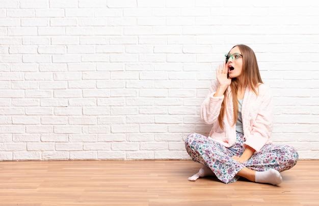 Jeune femme jolie vue de profil, l'air heureux et excité, criant et appelant à copier l'espace sur le côté. concept de maison
