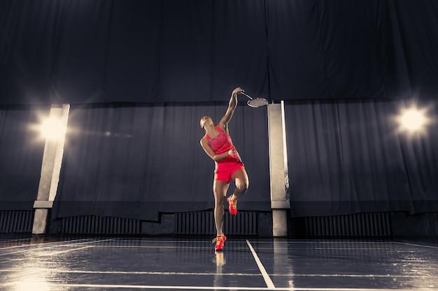 Jeune femme jouant au badminton au gymnase