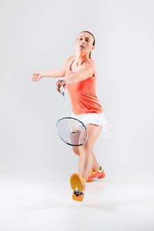 Jeune femme jouant au badminton sur blanc