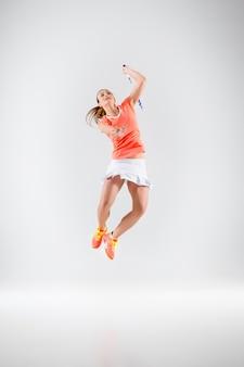 Jeune femme jouant au badminton sur mur blanc