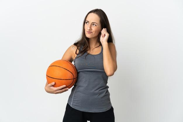 Jeune femme jouant au basket-ball sur fond blanc isolé frustré et couvrant les oreilles