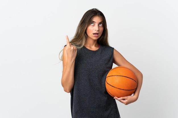 Jeune femme jouant au basket-ball isolé sur fond blanc pensant à une idée pointant le doigt vers le haut